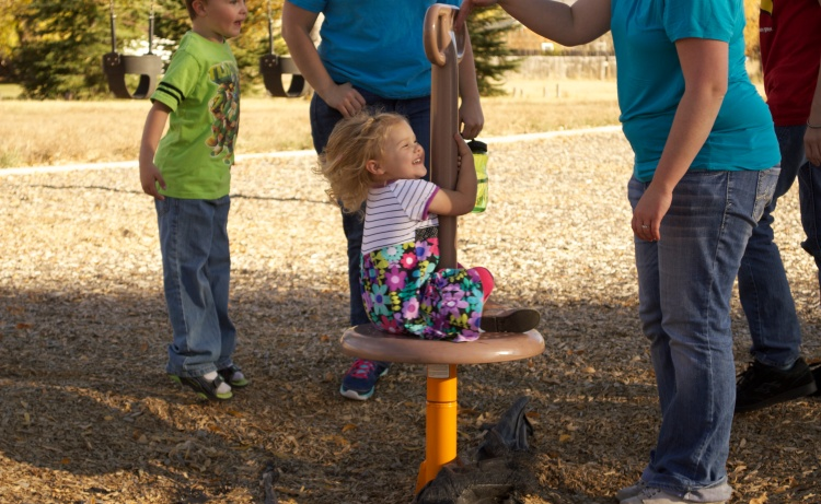A toddler laughs in enjoyment on the playground at the Greenbelt.